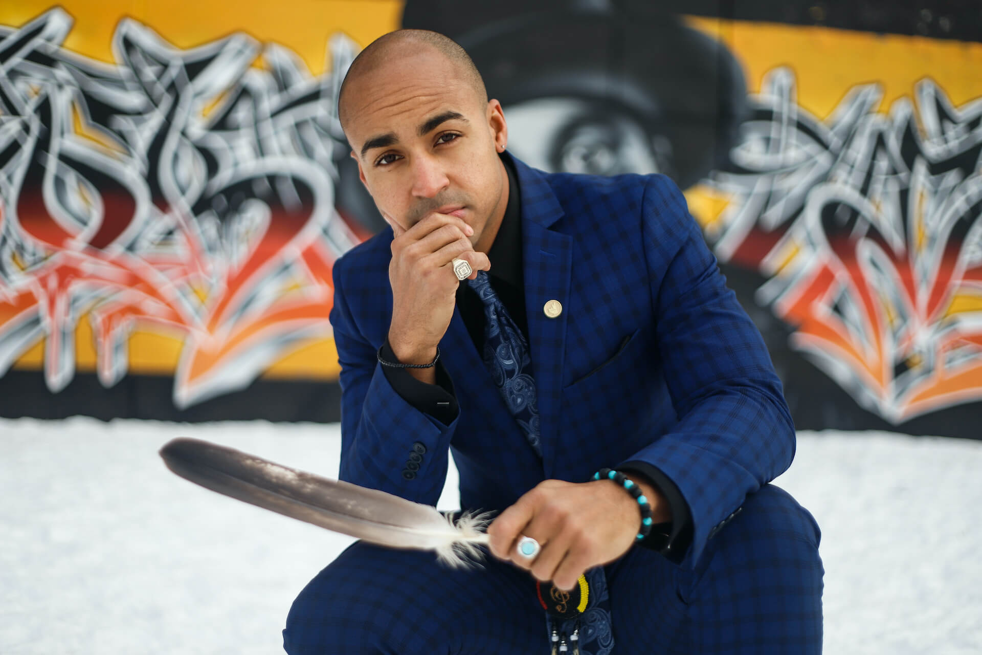 Close-up photo of Justin in a suit, in front of a wall of graffiti, holding a feather
