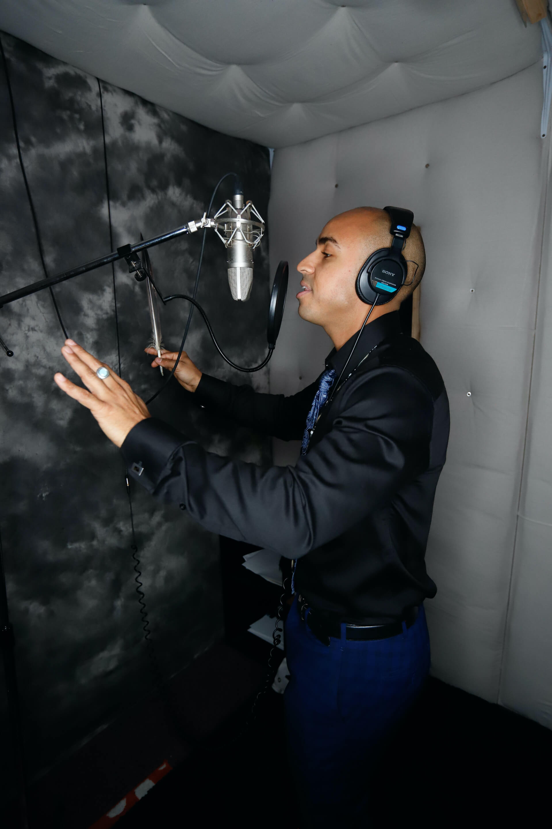 Photo of Justin recording a song in his recording-studio