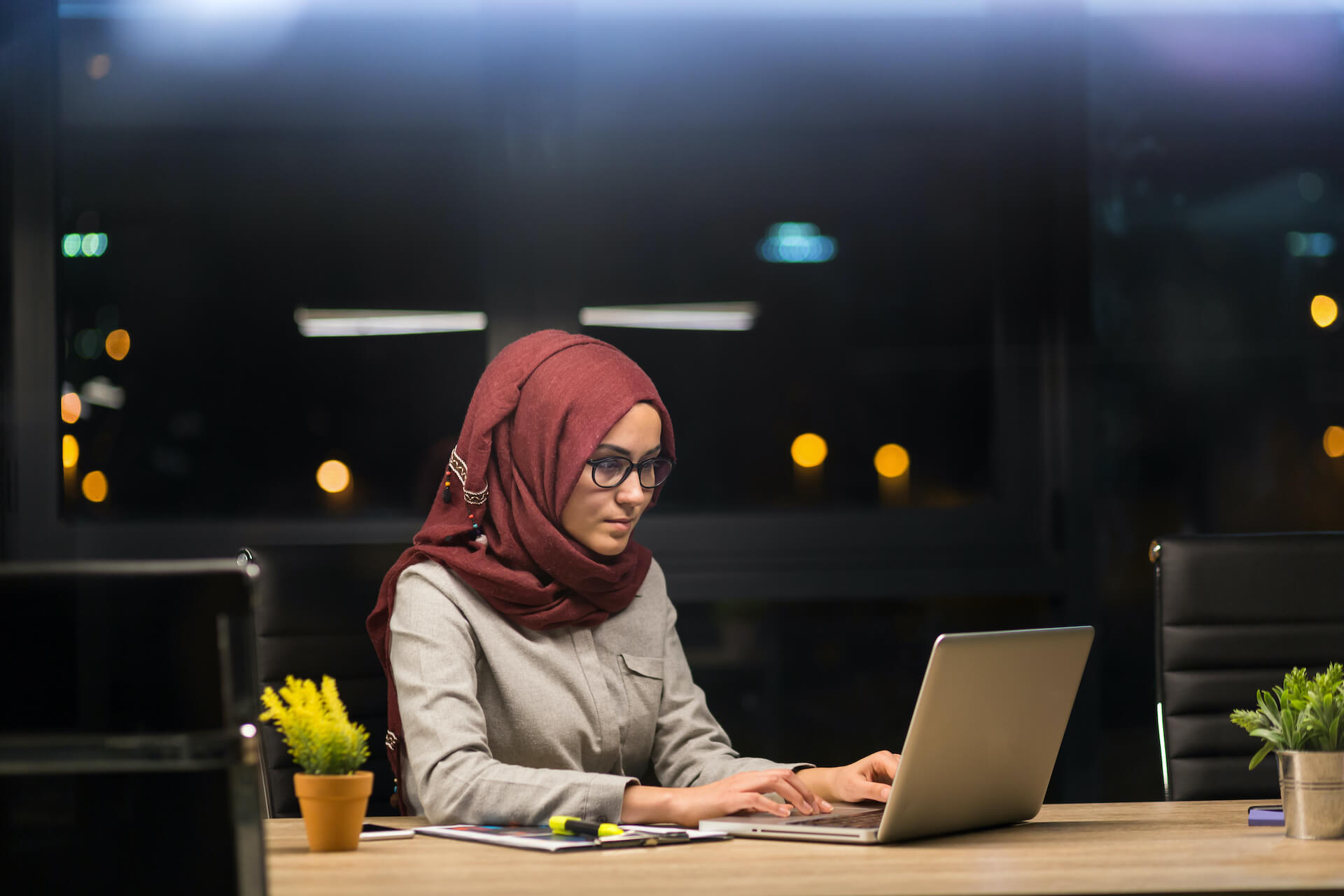 woman wearing a hijab working at an office